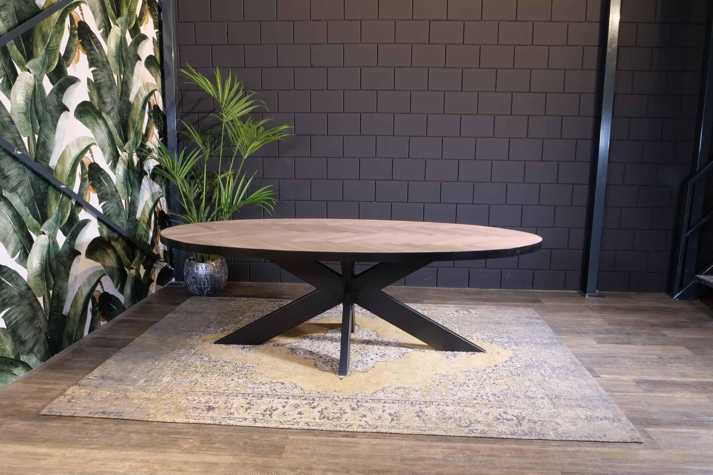 Ovale visgraat tafel met zwart stalen rand
